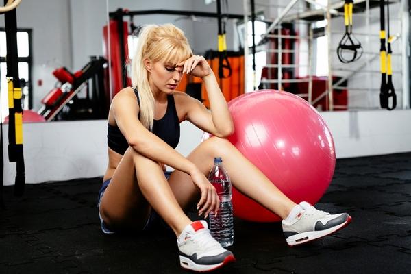 девушка сидит на полу в спортзале