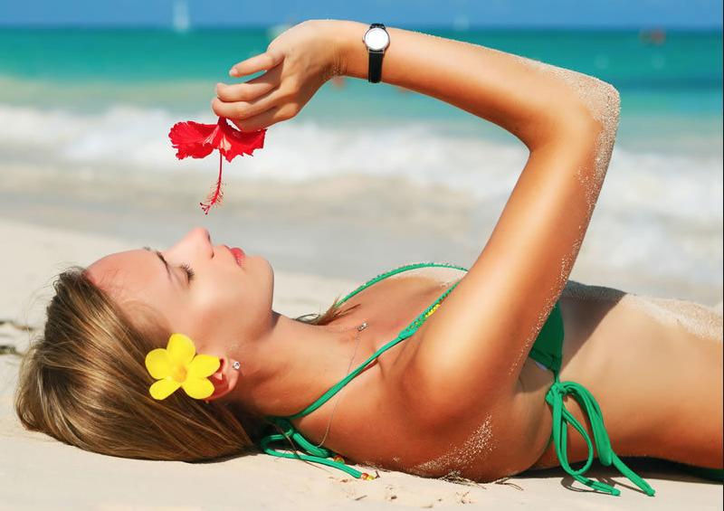 девушка лежит на пляже с цветком
