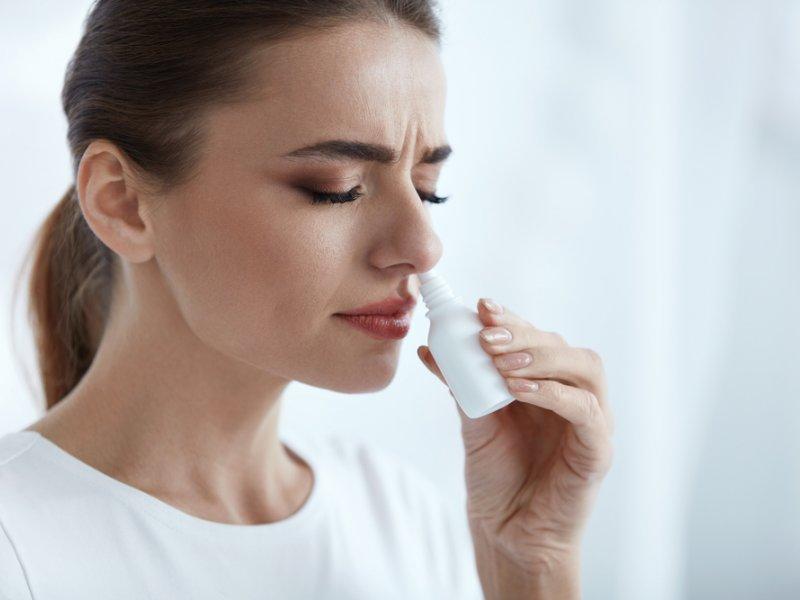 женщина пользуется спреем для носа