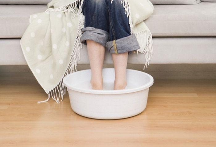 девушка держит ноги в тазу
