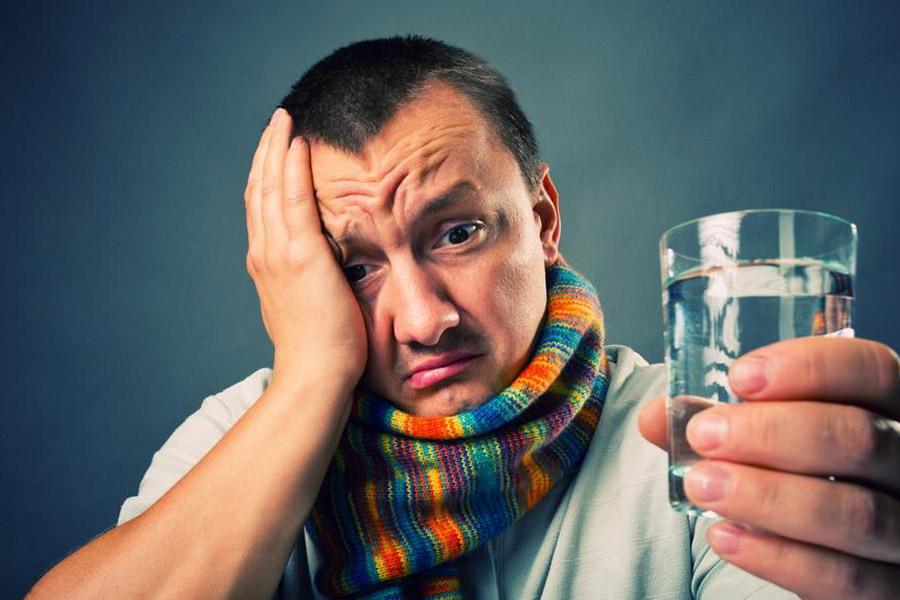 мужчина в шарфе со стаканом воды