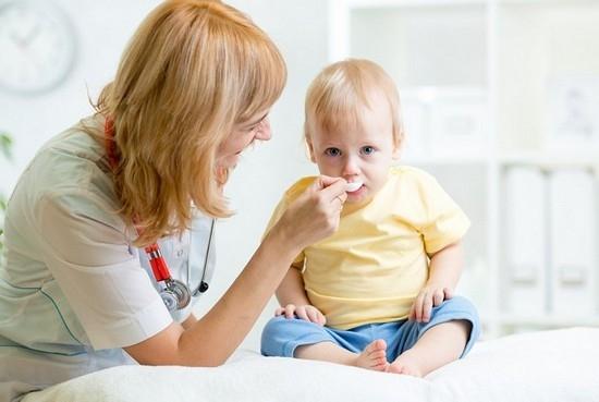 доктор кормит малыша лекарством