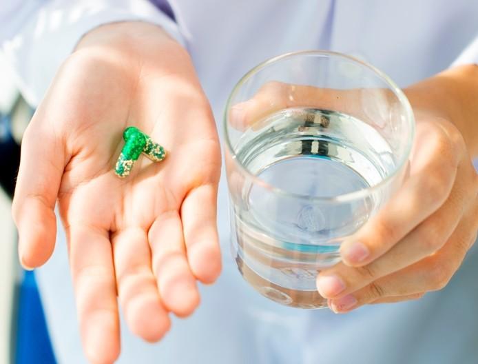 врач держит таблетку и стакан с водой