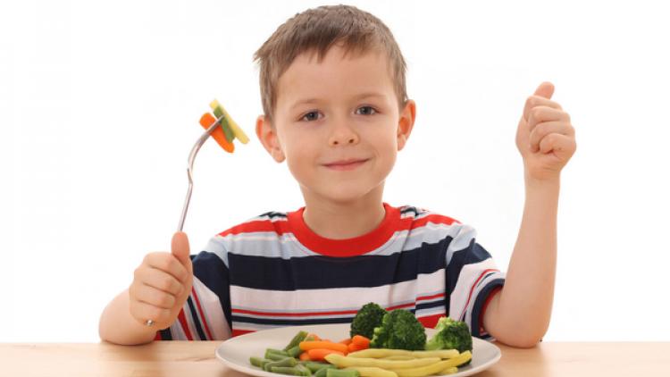 мальчик ест овощи