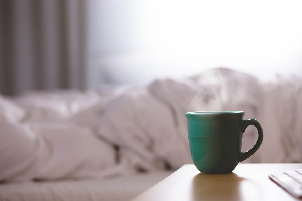чашка на фоне кровати